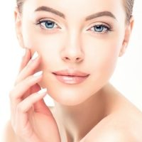 lady touching face lux glow facial services